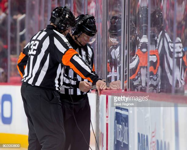 Referee's Tom Kowal and Dennis LaRue review a goal by Tom Pyatt of the Ottawa Senators during an NHL game against the Detroit Red Wings at Little...