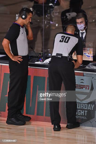 Referees Zach Zarba and John Goble look on during a replay during Game Four of the NBA Finals between the Los Angeles Lakers and the Miami Heat on...