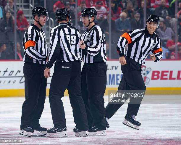 Refereeu2019s Kevin Pollock Jean Hebert and Linsemen Steve Miller and Libor Suchanek gather at center ice for the start an NHL game between the...