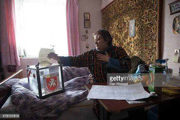 Referendum staff collect the vote of Shumitskaya Irina who was too infirm to visit the polling station in a predominantly Russian area of...