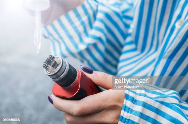 refill the cartridge with an electronic cigarette - hitech mod a stock pictures, royalty-free photos & images