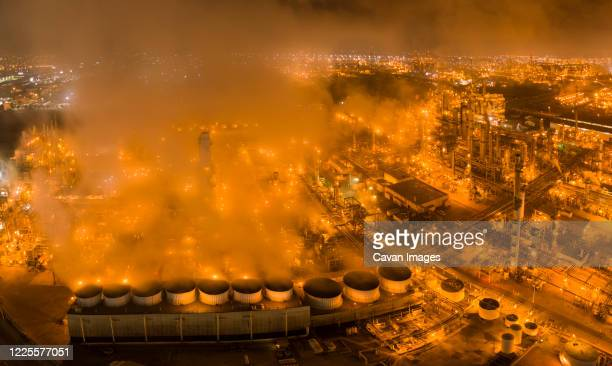 refinery and steam glowing orange in night aerials - carson california stock pictures, royalty-free photos & images