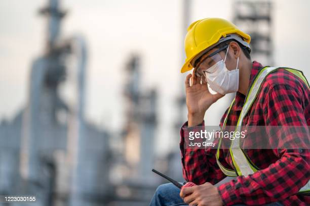 refinery industry engineer  wearing co protective coronavirus disease starting in 2019 or covid-19mask sading because because of being unemployed - danger stock pictures, royalty-free photos & images