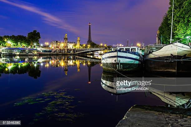 Reflect at blue hour of houseboats and Alexandre III bridge in Paris, France