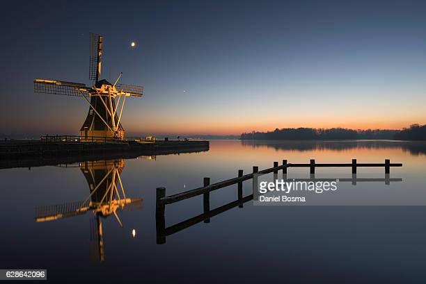 reflected historical windmill during colorful sunset - groningen stockfoto's en -beelden