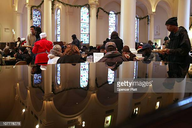 Reflected on a church piano, people eat a Christmas holiday meal at the Holy Apostles Soup Kitchen on December 24, 2010 in New York City. The soup...
