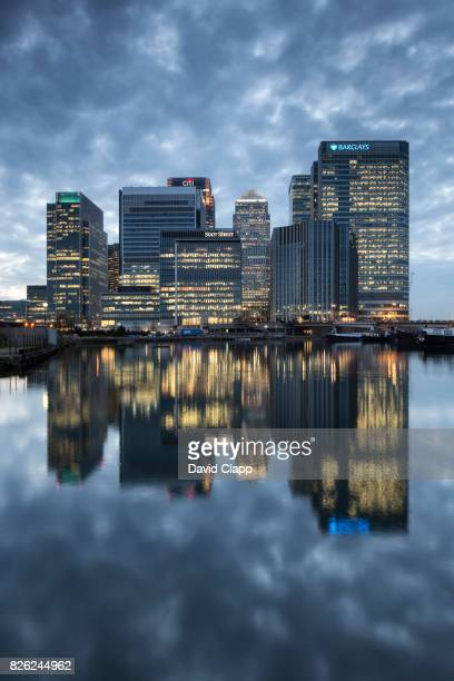 reflected skyline of canary wharf at dusk - canary wharf stock pictures, royalty-free photos & images