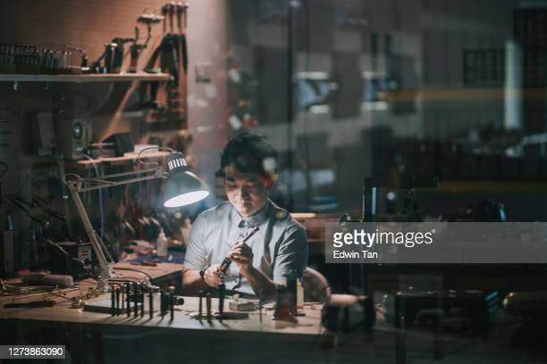 reflection Asian chinese man checking and repairing Soprano saxophone music wind instrument in his workshop