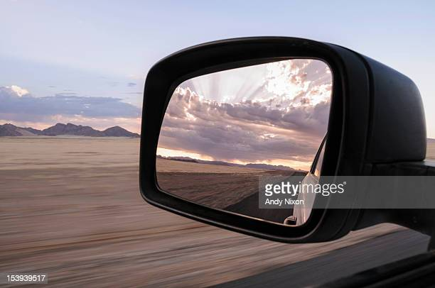 Reflection in a car rear-view mirror of a sunrise through the clouds of a rain storm over a distant mountain range, flat road through dry desert in foreground, motion blur, Sossusvlei, Namib Desert, Namib-Naukluft National Park, Namibia