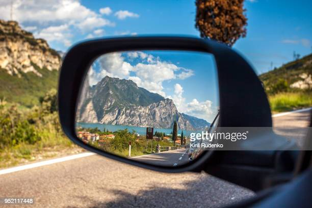 a reflection in a car's mirror at lake garda, italy - vehicle mirror stock photos and pictures