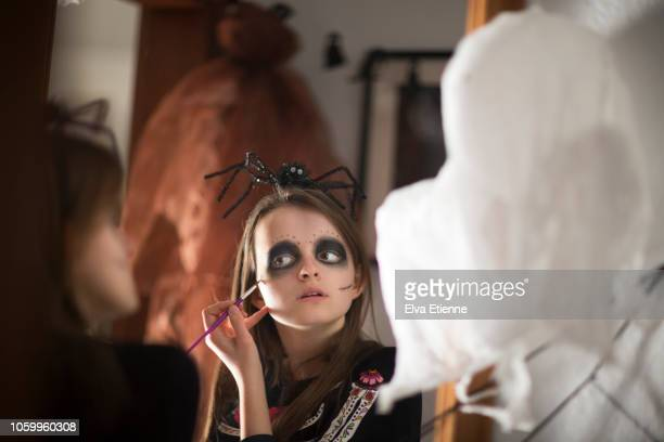 reflection in a mirror of a teenage girl applying halloween face paints to herself - naughty halloween stock photos and pictures
