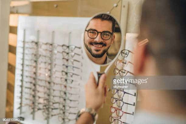 reflection in a mirror of happy man choosing eyeglasses at optician's. - hand mirror stock pictures, royalty-free photos & images
