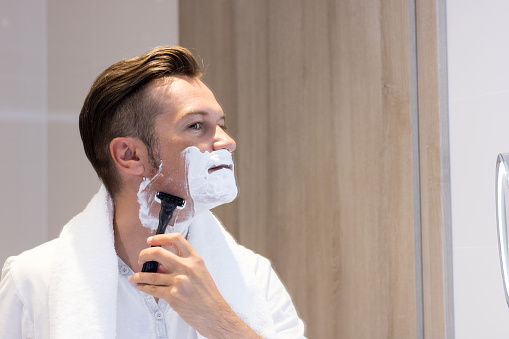 Reflection in a mirror of man shaving his face. 988633816