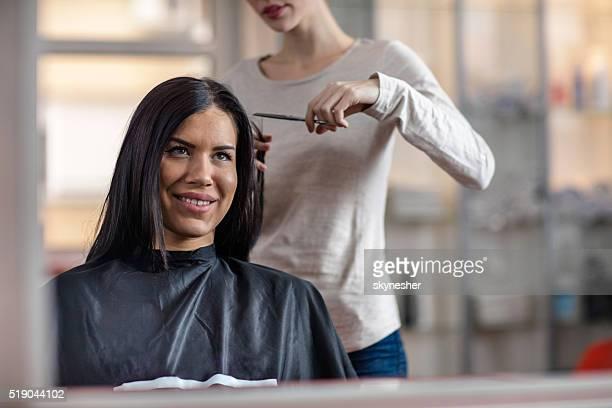 Reflexion in einem Spiegel der lächelnde Frau, die Haare schneiden.