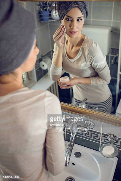 Reflection in a mirror of woman cleaning face in bathroom.