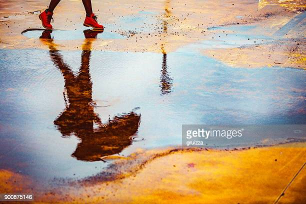 reflection in a puddle of a young woman holding umbrella, walking outdoors on a cold, windy, rainy autumn day. - puddle stock pictures, royalty-free photos & images