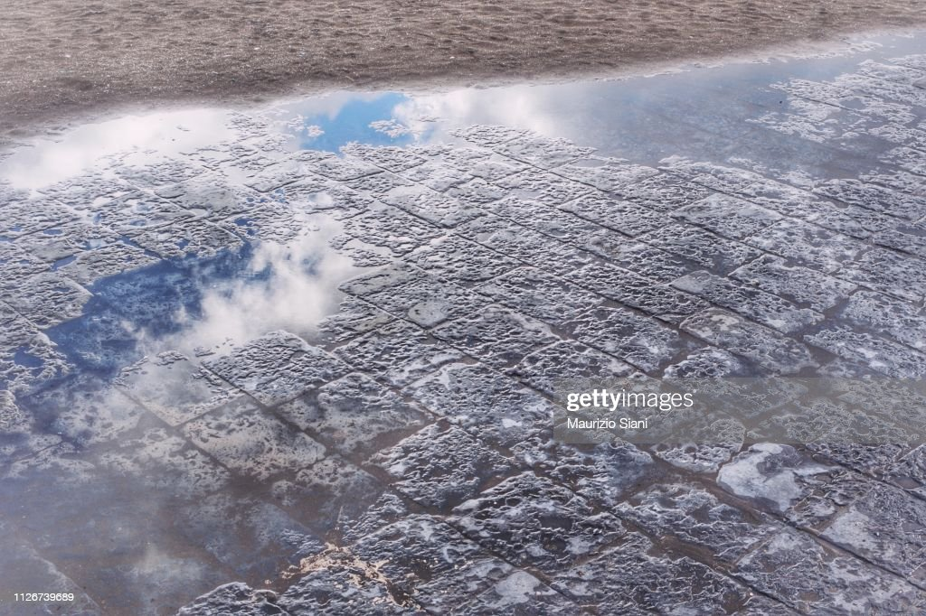 Reflection in a puddle of clouds in the rain : Stock Photo