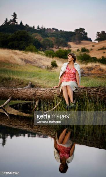 reflection in lake of caucasian woman sitting on log - log stock pictures, royalty-free photos & images