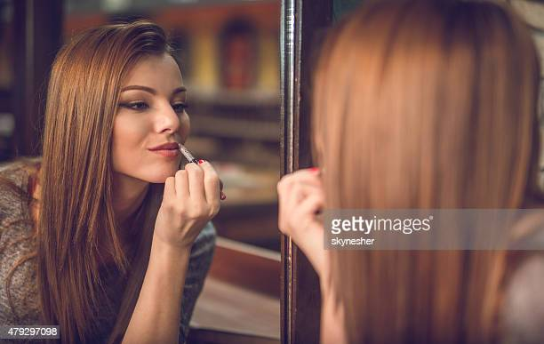 reflection in mirror of a beautiful woman applying lipstick. - lip liner stock photos and pictures
