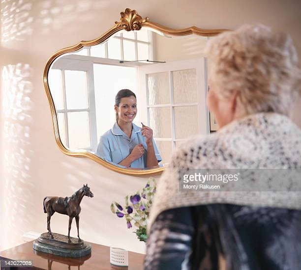 Reflection in mirror of nurse holding key to senior woman's house