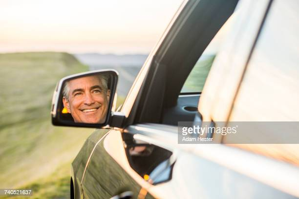 reflection in mirror of smiling caucasian man driving car - side view mirror stock photos and pictures