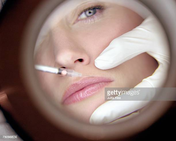 Reflection in mirror of surgeon giving woman a neurotoxin injection injection
