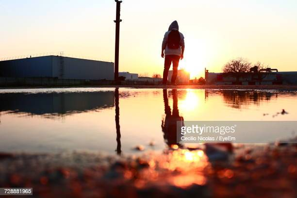 Reflection In Puddle In City During Sunset