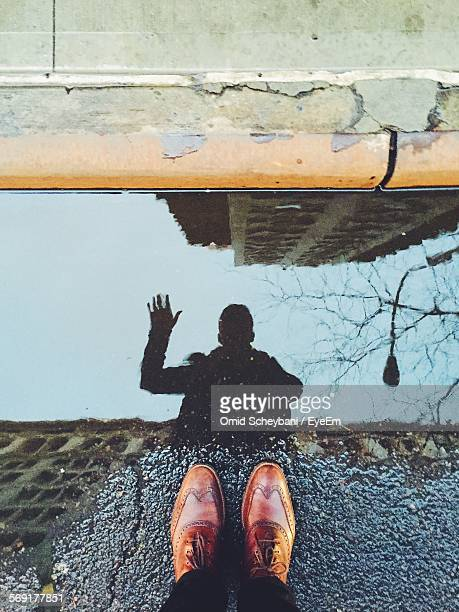 Reflection in puddle of man waving hand and photographing