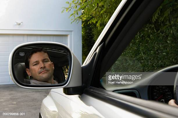 Reflection in rear view mirror of man reversing car on driveway