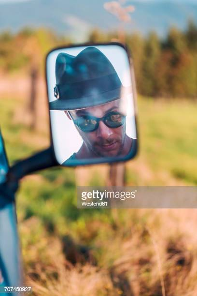 Reflection in rear-view mirror of man wearing a hat and sunglasses
