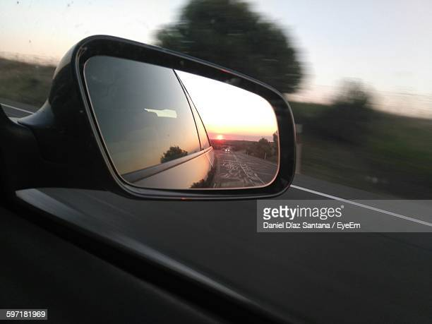 Reflection In Side-View Mirror Of Car At Street