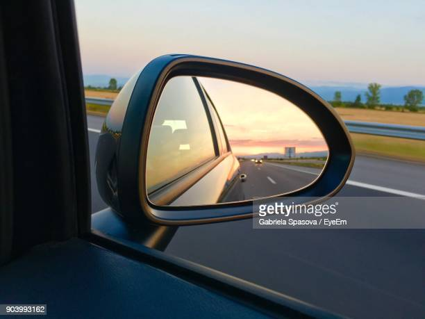reflection in side-view mirror of car - vehicle mirror stock photos and pictures