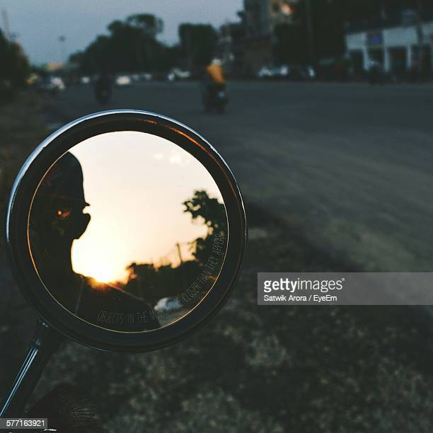 Reflection In Side-View Mirror Of Motorcycle On Street