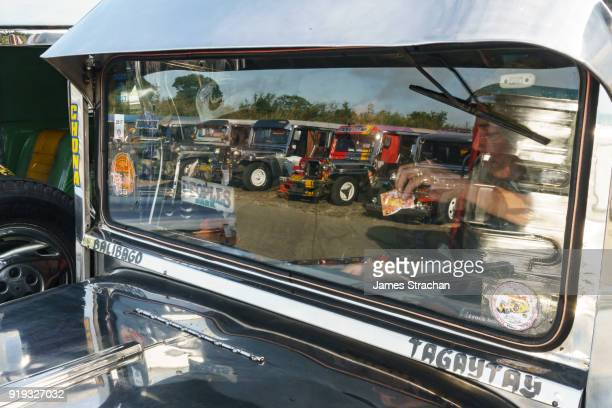 Reflection in the front window of a jeepney, the most popular means of public transport in the Philippines, as the driver takes money and prepares to leave the jeepney terminal. Their kitsch decorations are a ubiquitous symbol of popular art, Tagaytay, Lu