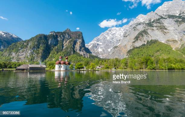 reflection in the water, koenigssee lake with watzmann massif and pilgrimage church of st. bartholomew, national park berchtesgaden, berchtesgadener, upper bavaria, bavaria, germany - berchtesgaden national park stock photos and pictures