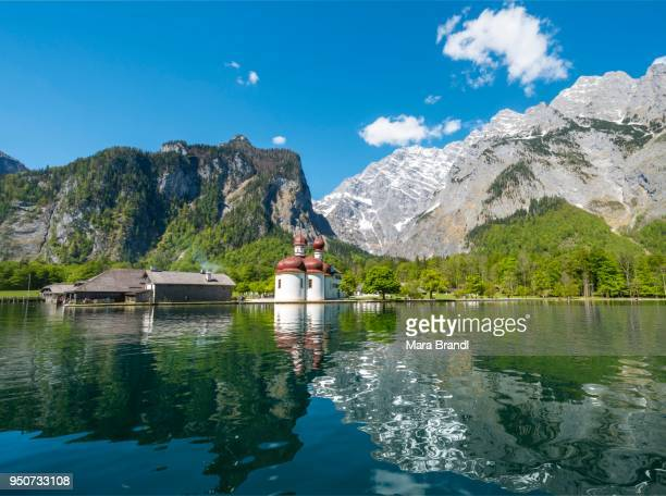 reflection in the water, koenigssee with pilgrimage church st. bartholomew and watzmann massif, national park berchtesgaden, berchtesgaden, upper bavaria, bavaria, germany - berchtesgaden stock pictures, royalty-free photos & images