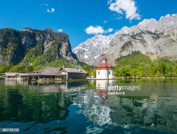 Reflection in the water, Koenigssee with pilgrimage church St. Bartholomew and Watzmann massif, National Park Berchtesgaden, Berchtesgaden, Upper Bavaria, Bavaria, Germany