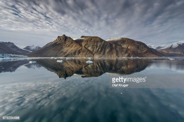 reflection in the water, mountains and icebergs, kaiser franz josef fjord, kejser franz josef fjord, northeast greenland national park, greenland - northeast stock photos and pictures