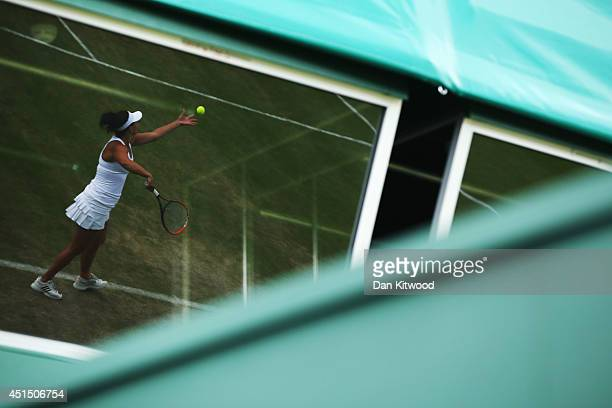 A reflection is seen in a window of Casey Dellacqua of Australia serving during her Ladies Doubles Second round match with Ashleigh Barty against...