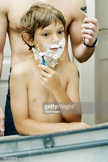 Reflection of a boy shaving in a mirror