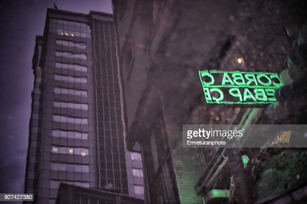 reflection of a building and led light restaurant sign on rainwater. - emreturanphoto stock pictures, royalty-free photos & images