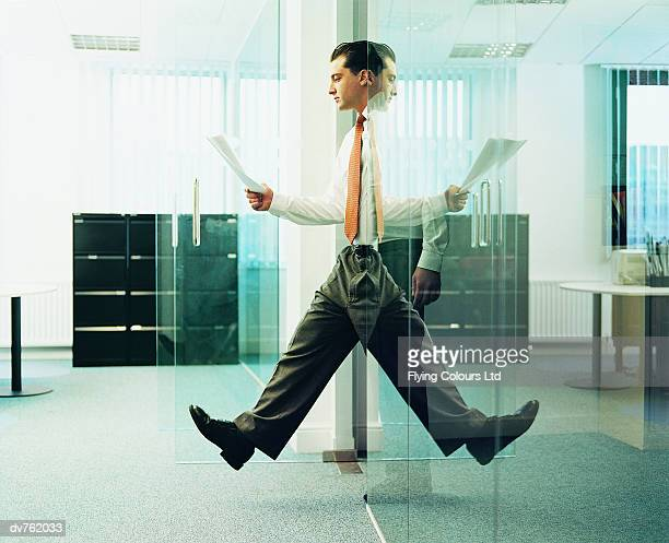 Reflection of a Businessman Walking out of an Office