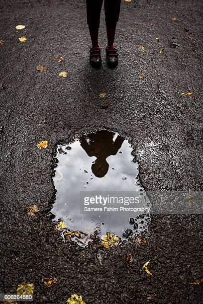 reflection of a girl in puddle - puddle stock pictures, royalty-free photos & images