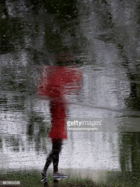 Reflection of a girl standing in street with umbrella