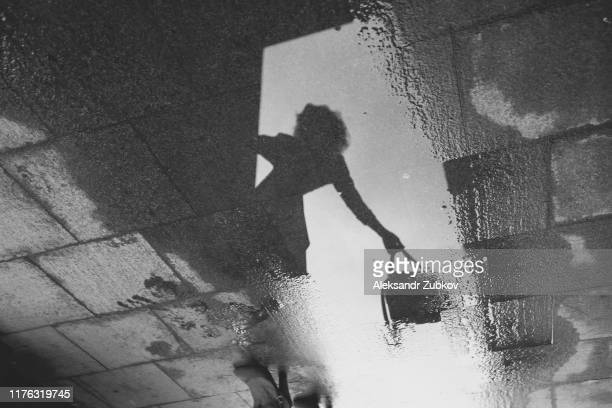 reflection of a girl with a bag in her hand in a puddle on a stone pavement. black and white - teenage girls feet stock-fotos und bilder
