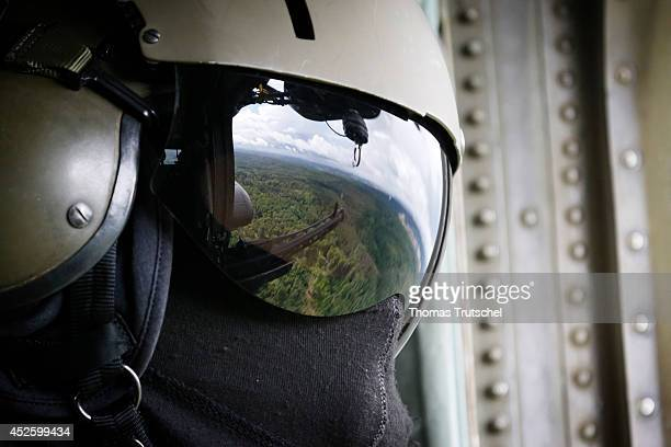 Reflection of a machine gun in the helmet visor of an aerial gunner who is standing in a Sikorsky CH53 Sea Stallion heavylift transport helicopter on...