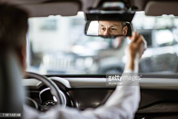 reflection of a man in a rear-view mirror while driving a car. - rear view mirror stock pictures, royalty-free photos & images