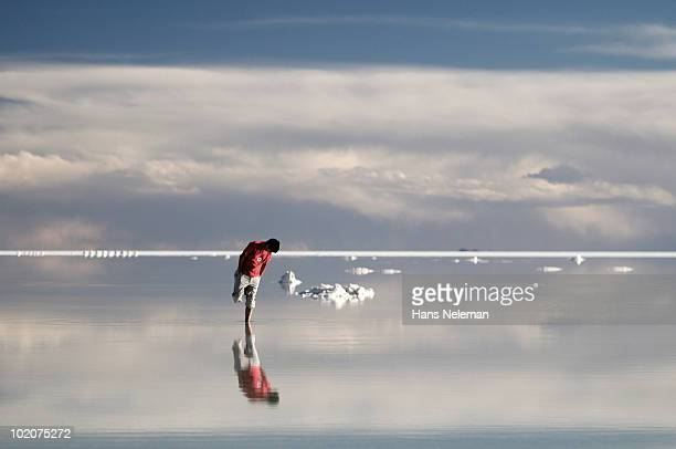Reflection of a man in water, Salar De Uyuni, Bolivia