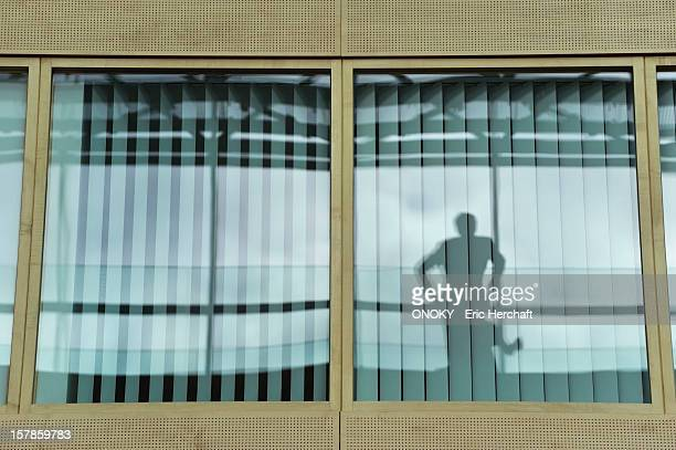 reflection of a person on the glass of an office window - onoky stock-fotos und bilder