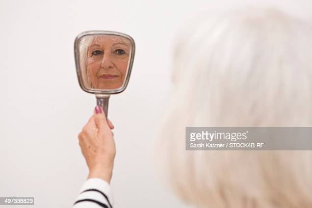reflection of a senior woman in hand mirror - hand mirror stock pictures, royalty-free photos & images